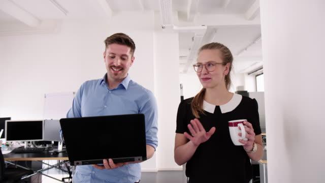 オフィスで歩いたり話したりする仕事仲間 ビデオ
