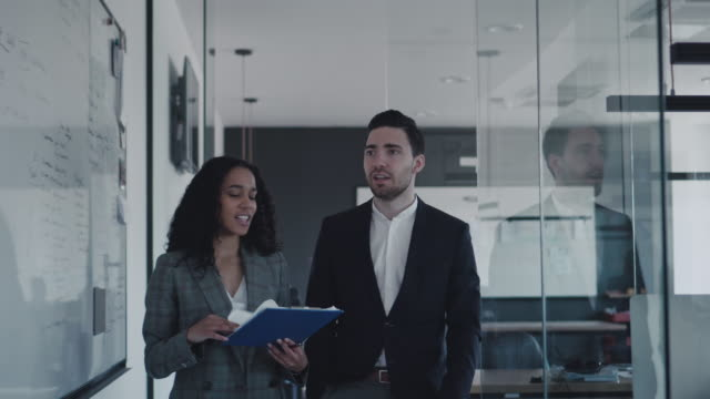 stockvideo's en b-roll-footage met zakelijke collega's lopen door het kantoor en praten over nieuwe project - mid volwassen vrouw