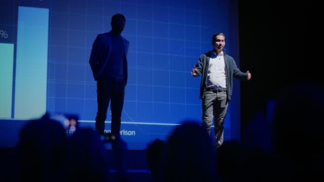 business conference stage: indian tech startup ceo präsentiert das neueste produkt der firma, he es holding laptop und macht motivationsgespräch über wissenschaft, technologie, softwareentwicklung und führung - zuschauerraum stock-videos und b-roll-filmmaterial