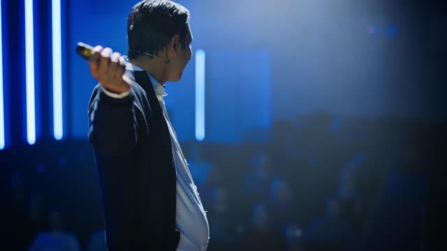 business conference stage: software developer, startup ceo präsentiert neues produkt, macht motivationsgespräch. referent hält vortrag über wissenschaft, technologie, unternehmertum, entwicklung, führung - zuschauerraum stock-videos und b-roll-filmmaterial