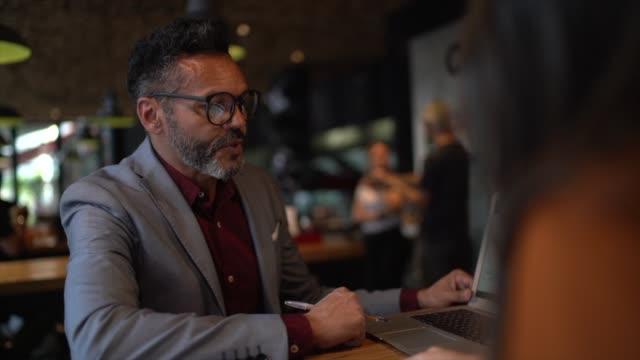 affärskonsult på ett möte på cafeteria - accounting bildbanksvideor och videomaterial från bakom kulisserna