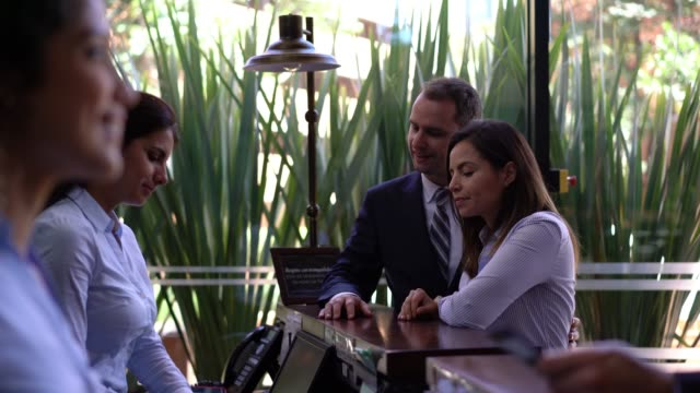 Business couple checking into a hotel and friendly receptionist handing the key