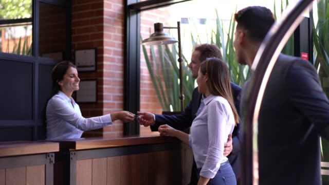 Business couple checking into hotel with the help of receptionist and bellboy carrying their bags Business couple checking into hotel with the help of receptionist and friendly bellboy carrying their bags on cart hotel stock videos & royalty-free footage