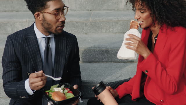 Business couple enjoying lunch break outdoors