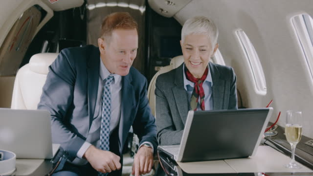 Business couple in private jet airplane Senior couple sitting inside private jet airplane and working during the flight. private airplane stock videos & royalty-free footage