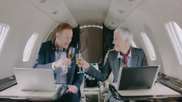 business-paar im privat-jet flugzeug - generaldirektor oberes management stock-videos und b-roll-filmmaterial