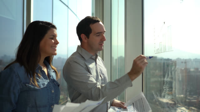 Business couple planning something using the window to write with a felt tip marker and using documents