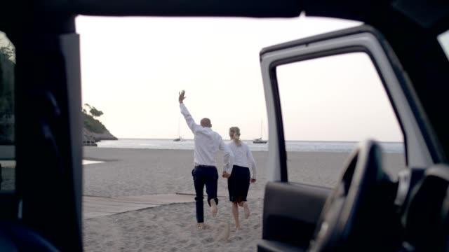 vidéos et rushes de couple d'affaires fuyant la voiture à la plage - homme faire coucou voiture
