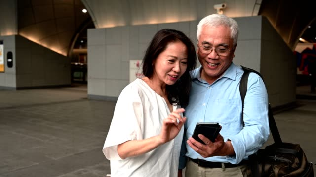 business couple with cellphone at subway station - 60 69 anni video stock e b–roll