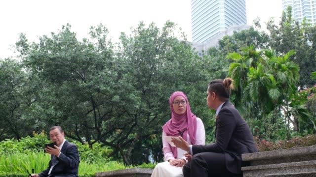 business discussion in the park - abbigliamento religioso video stock e b–roll