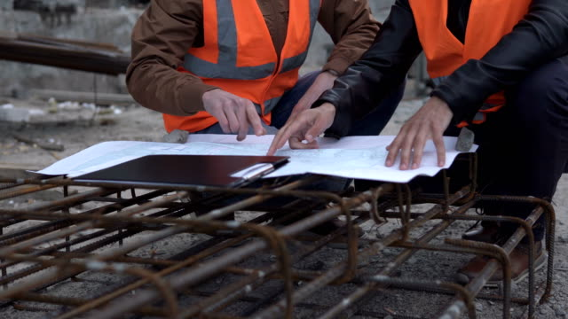 Business engineering at a construction site. Discussion of the construction drawing in the field on the construction of a high-rise building. video