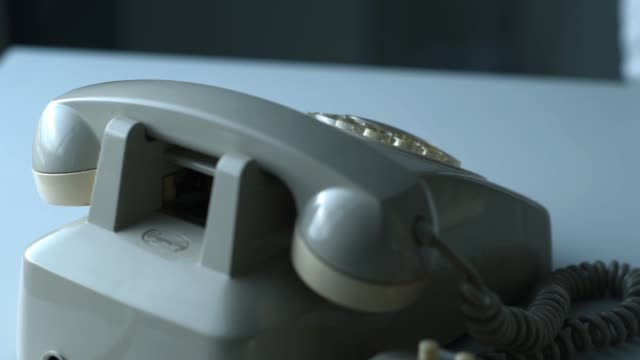 Business executive dialing a number on a vintage rotary dial phone and holding the receiver, hands close up Business executive dialing a number on a vintage rotary dial phone and holding the receiver, hands close up telephone receiver stock videos & royalty-free footage