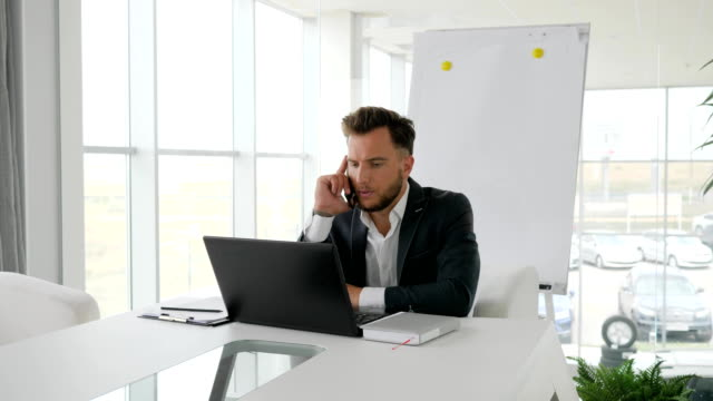 business executive talk on mobile to workplace in modern office, serious businessman Works on laptop at Internet video