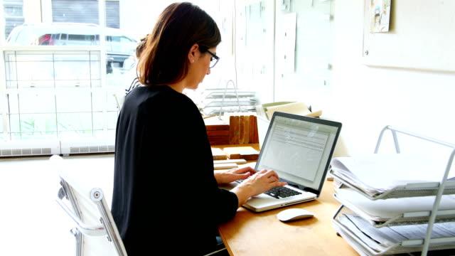 vidéos et rushes de dirigeant d'entreprise à l'aide d'ordinateur portable - pots de bureau