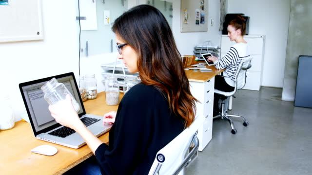 vidéos et rushes de dirigeant d'entreprise à l'aide d'ordinateur portable tout en tenant le bocal de cailloux - pots de bureau
