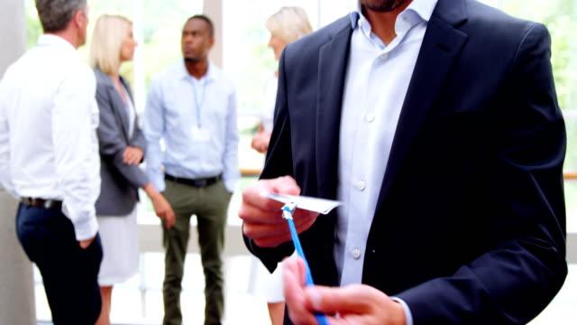 vídeos de stock e filmes b-roll de business executive wearing id card - badge