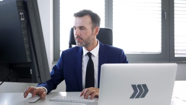 Business executive working in office with computer and then looking at camera Business executive working in office with computer and then looking at camera ceo stock videos & royalty-free footage
