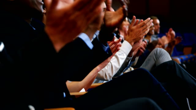 Business executives applauding in a business meeting