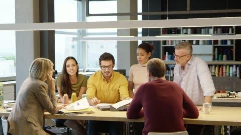 vidéos et rushes de cadres d'affaires discutant sur des échantillons de tissu - 20 secondes et plus