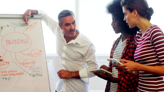 Business executives discussing over flip chart during meeting 4k video