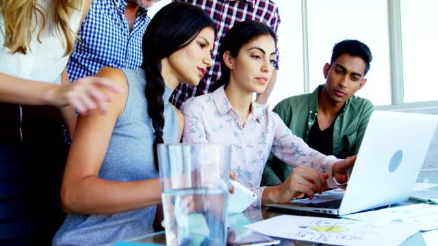 business executives discussing over laptop 4k - hindus filmów i materiałów b-roll