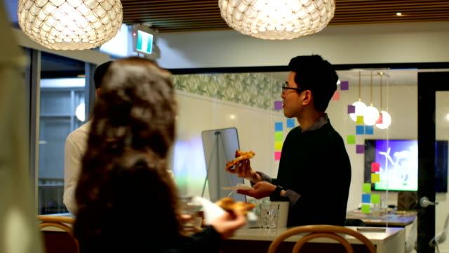 vídeos de stock e filmes b-roll de business executives eating pizza in office cafeteria 4k - cantina