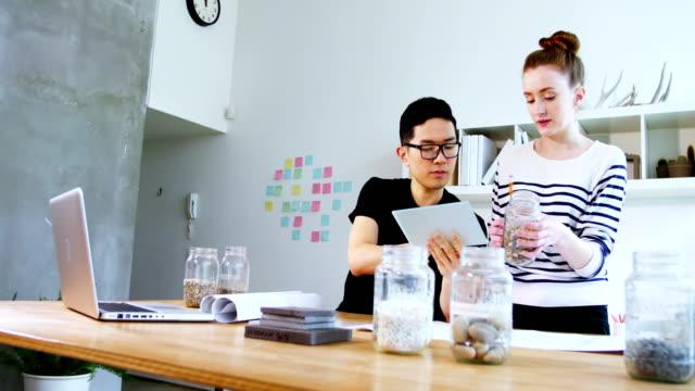 vidéos et rushes de les voyageurs d'affaires à l'aide de tablette numérique - pots de bureau