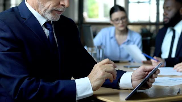 бизнес-эксперт обдумывает решение, держа планшет, квалифицированный консалтинговый сервис - expert стоковые видео и кадры b-roll