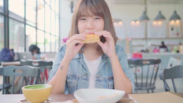 フリーランス アジア女性実業家パンを食べると温かい一杯のコーヒーを飲みながらカフェでテーブルの上に座って。ライフ スタイル スマート美しい女性は、コーヒー ショップの概念でリラ ビデオ
