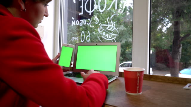 business girl in a coffeshop, working using laptop and phone video