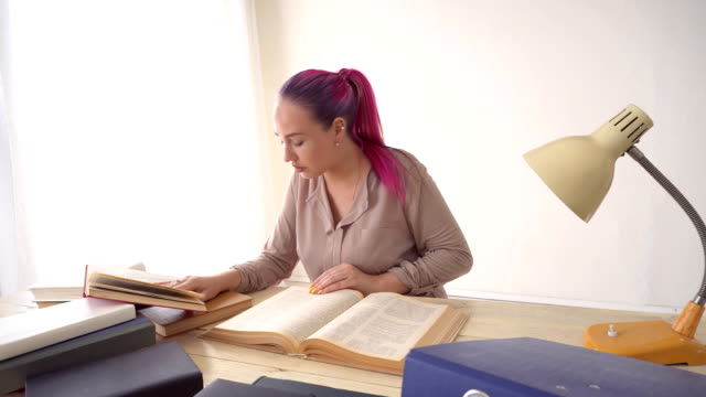 business girl sits in the Office for books folders of paper Secretary video