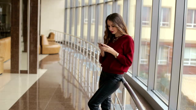 Business girl standing in a modern building near the window with phone in hand. video