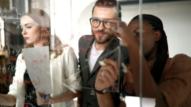 Business group Writing Ideas On Glass Screen During Meeting video