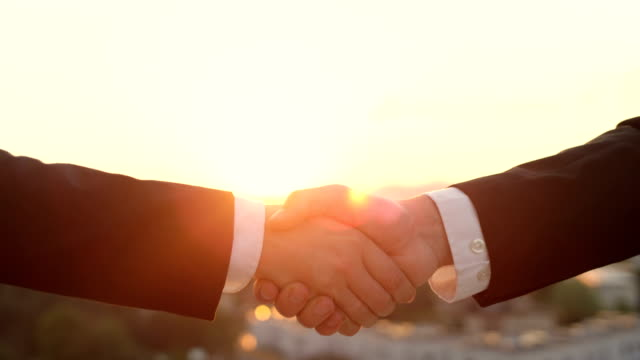 CLOSE UP: Business hand shake at sunset with beautiful cityscape in background video