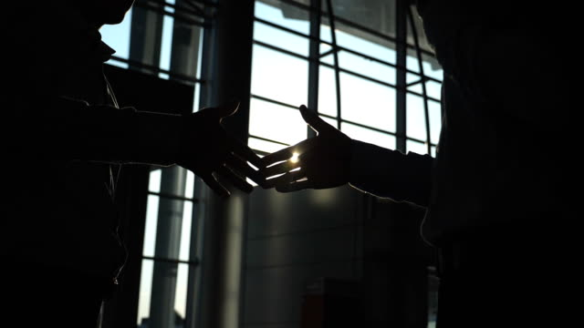Business handshake indoor at office with sun flare at background. Silhouette of two businessmen greeting each other. Handclasp of partners inside. Colleagues meet and shake hands. Close up Slow motion Low angle view video