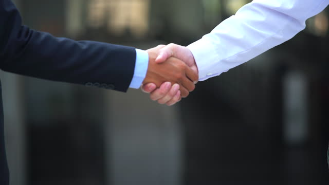 Business handshake of two men demonstrating their agreement to sign agreement or contract between their firms / companies / enterprises. video