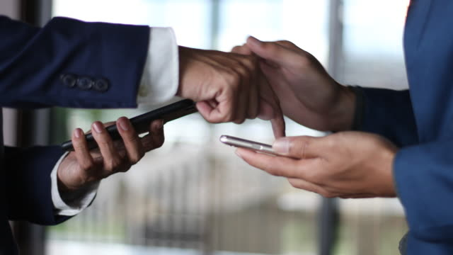 Business Handshake two businessman shaking hands  and using smartphone video