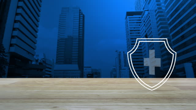 Business healthy and medical care insurance concept Cross shape with shield flat icon on wooden table over modern office city tower and skyscraper, Business healthy and medical care insurance concept shield stock videos & royalty-free footage