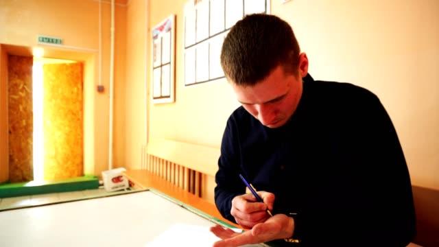 Ein Geschäft in einem Hemd schreibt etwas auf seinem Arm mit einem Stift. – Video