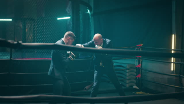 Business is a tough play. Two angry businessmen throwing punches in octagon