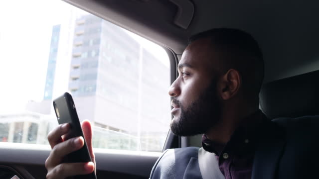 Business is about traveling and making connections 4k video footage of a handsome young businessman using his cellphone while traveling in the backseat of a car business goals stock videos & royalty-free footage