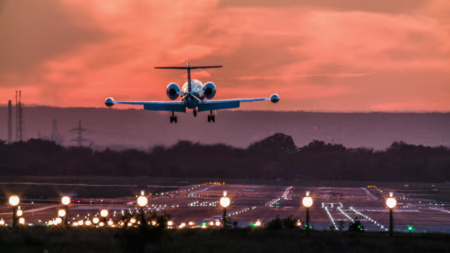 stockvideo's en b-roll-footage met business jet landing op de luchthaven runway at dusk - vliegtuig