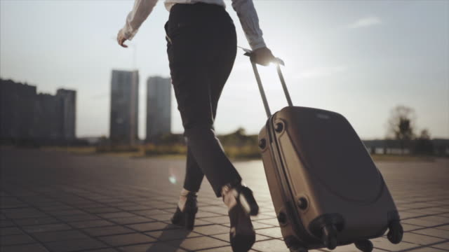 business lady going to taxi parking from the airport with her luggage. girl in heels stepping and roll suitcase on wheels. woman walking with her suitcase along street. travel concept. slow motion - табло вылетов и прилётов стоковые видео и кадры b-roll