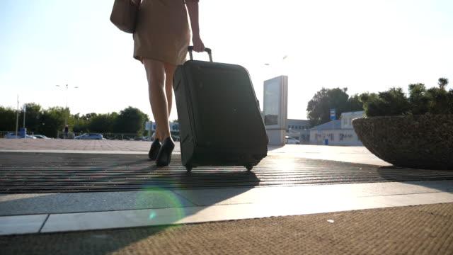stockvideo's en b-roll-footage met business lady gonna taxi parkeren van de luchthaven met haar bagage. jong meisje in hakken intensivering en glooiende koffer op wielen. vrouw met haar bagage langs straat wandelen. travel concept. slow motion dicht omhoog terug achteraanzicht - parkeren