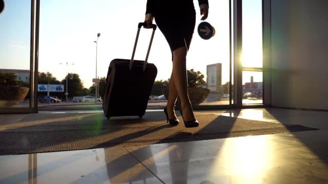 vídeos de stock, filmes e b-roll de mulher de negócios vai para o aeroporto com a bagagem. jovem mulher de saltos altos entrar andando através de portas de vidro para o terminal e rolo mala com rodas. conceito de viagens viagem ou férias. movimento lento fechar - perna termo anatômico