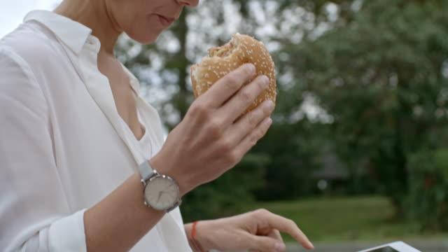 vídeos de stock, filmes e b-roll de mulher de negócios com tablet comendo hambúrguer ao ar livre - junk food