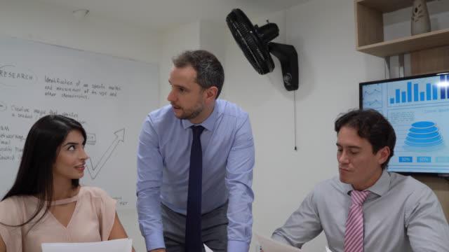 vídeos y material grabado en eventos de stock de líder de negocios dirigiéndose a su equipo en la sala de conferencias mientras sostenía el papeleo todo buscando muy centrado - zoom meeting