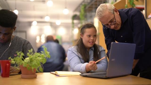 vídeos y material grabado en eventos de stock de liderazgo empresarial trabajando junto con la mujer de necesidades especiales dando algunos consejos - consejero de la escuela