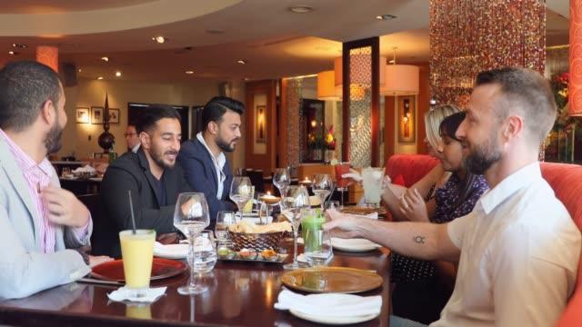 会議成功後のグループとのビジネスランチ - インド料理点の映像素材/bロール