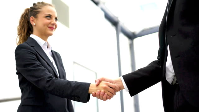 Business man and woman handshake at office video